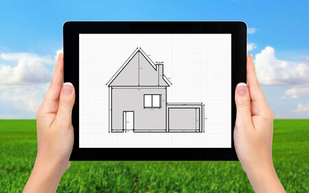 hands holding house: female hands holding a tablet computer with a drawing of apartment house on the screen background of green grass and blue sky Stock Photo