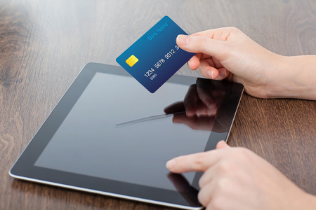 female hands holding credit card and a computer tablet on the table in the office photo