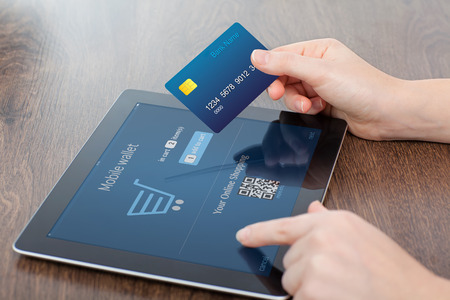 technology transaction: female hands holding credit card and a computer tablet on the table in the office and making a purchase onlain