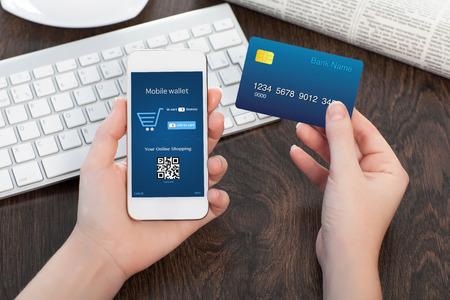 vrouwelijke handen houden van een creditcard en een touch telefoon op de tafel in het kantoor en het maken van een aankoop onlain Stockfoto