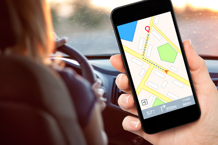 female hand holding a phone with interface navigator on a screen on a background woman driving a car photo