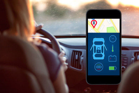 computer control: phone with interface auto alarm on a screen on a background woman driving a car