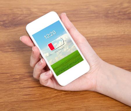 bateria: mano de mujer con un teléfono blanco contacto con la batería baja en la pantalla en el contexto de una mesa de madera