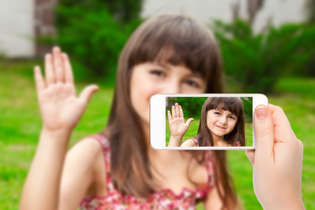 female hand holding a phone with video call of little girl on the screen on a background of green grass photo