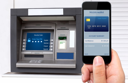 man hand holding the phone with mobile wallet and credit card on the screen against the background of the ATM Zdjęcie Seryjne