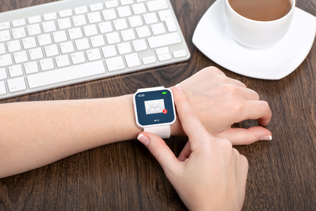 female hand with white smartwatch with email on the screen over a wooden table in an office Stock Photo