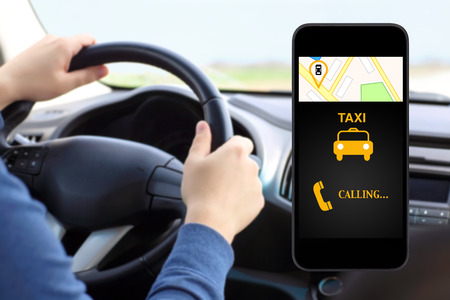 phone with interface taxi on a screen on a background man driving a car Stock Photo