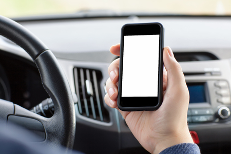 man sitting in the car and holding a touch phone with isolated screen  photo