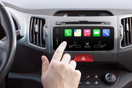 man sitting in a car and touch play finger in a auto smart system  Reklamní fotografie