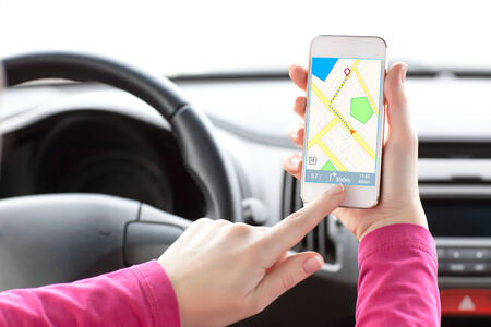 female driver hand holding a phone with interface navigator on a screen  Stock Photo