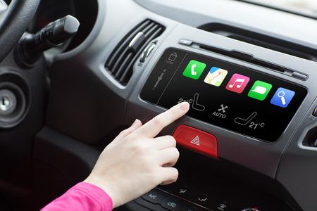 žena sedí v autě a klepněte na tlačítko Přehrát prstem na auto inteligentní systém