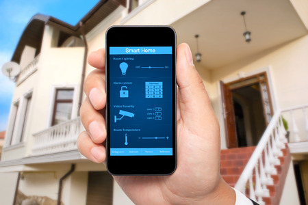 mannelijke hand houden van een telefoon met het systeem slimme huis op een scherm op de achtergrond van het huis