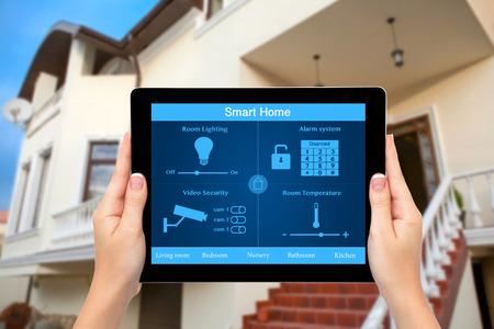 Vrouwelijke handen een tablet-computer met systeem slimme huis op een scherm op de achtergrond van het huis