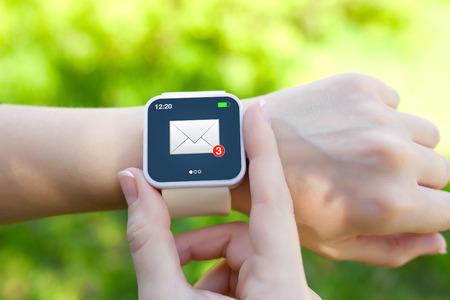Isolierte weiblichen Hände mit weißen Smartwatch mit E-Mail auf dem Bildschirm auf einem Hintergrund von grünem Gras