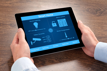 businessman holding a tablet computer with system smart house over the villages table photo