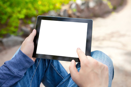media gadget: man sitting in the park and holding tablet computer with isolated screen