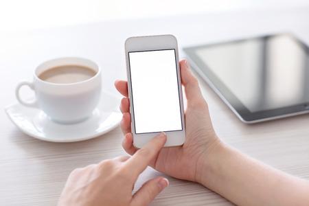 Vrouwen handen die de witte telefoon met geïsoleerde scherm boven de tafel met een kopje koffie en tablet