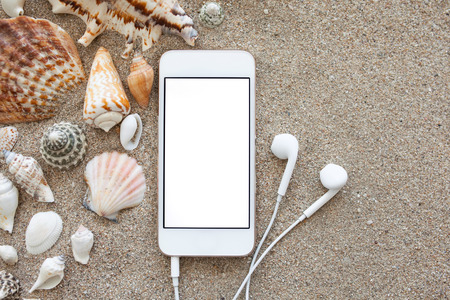 phone with isolated screen and headphones lying on the sand with shells