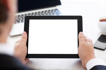 tablet devices: businessman holding a tablet with isolated screen over a table in the office