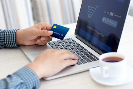 comprando: hombre que hace compras en l�nea con tarjeta de cr�dito en la computadora port�til