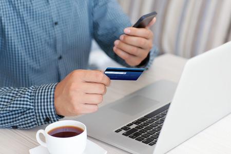男はラップトップと持株電話でクレジット カードによりお支払い