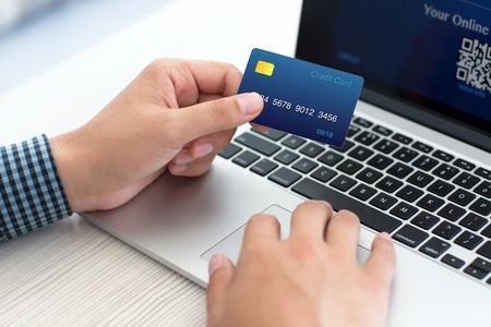 クレジット カードのラップトップ上でオンライン ショッピングをしている男 写真素材