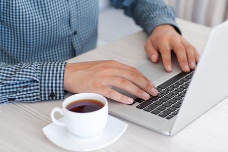 Man typen op een laptop toetsenbord in het kantoor Stockfoto