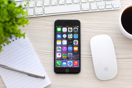 Alushta, Russia - October 25, 2014: New phone iPhone 6 Space Gray with apps on screen lies on the table. iPhone 6 was created and developed by the Apple inc.