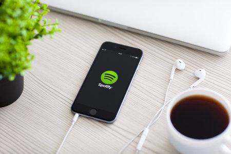 developed: Alushta, Rusia - 24 de octubre 2014: Tel�fono iPhone 6 Gris Espacial con servicio de m�sica Spotify en la pantalla sobre la mesa. iPhone 6 fue creado y desarrollado por Apple inc.
