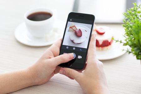 social networking service: Alushta, Rusia - 28 de octubre 2014: Mujer que sostiene un Espacio Gris iPhone 6 con servicio de red social Instagram en la pantalla. iPhone 6 fue creado y desarrollado por Apple inc.