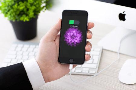 pila: Alushta, Rusia - 02 de noviembre 2014: Hombre que sostiene un espacio gris iPhone 6 con el icono de batería en la pantalla. iPhone 6 fue creado y desarrollado por Apple inc. Editorial