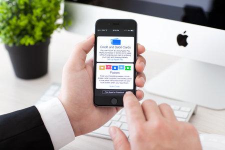 manzanas: Alushta, Rusia - 02 de noviembre 2014: El hombre de negocios la celebración de un Espacio Gris iPhone 6 con servicio de Apple Pago y Passbook en la pantalla. iPhone 6 fue creado y desarrollado por Apple inc.
