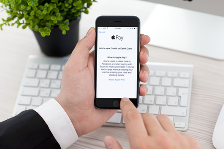 Alushta, Rusia - 03 de noviembre 2014: El hombre de negocios la celebración de un Espacio Gris iPhone 6 con servicio de Apple de pago en la pantalla. iPhone 6 fue creado y desarrollado por Apple inc. Editorial