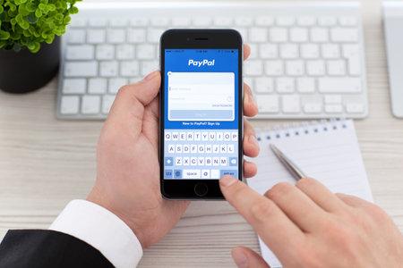 Alushta, Rusland - 3 november 2014: Zakenman die een iPhone 6 Space Gray met service PayPal op het scherm. iPhone 6 werd gecreëerd en ontwikkeld door Apple inc.