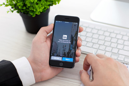 Alushta, Rusland - 3 november 2014: Zakenman die een iPhone 6 Space Grijs met sociale netwerkdienst LinkedIn op het scherm. iPhone 6 werd gecreëerd en ontwikkeld door Apple inc.