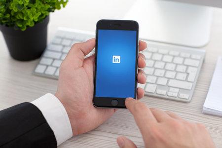 Alushta, Russie - 3 Novembre, 2014: Homme d'affaires tenant un iPhone 6 Espace gris avec un service de réseau social LinkedIn sur l'écran. iPhone 6 a été créé et développé par Apple inc. Éditoriale