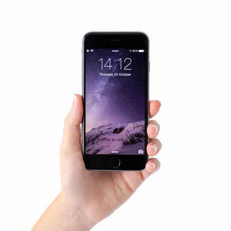Alushta, Rusia - 23 de octubre 2014: Mano de la mujer sosteniendo iPhone 6 Espacio gris con desbloqueo en la pantalla. iPhone 6 fue creado y desarrollado por Apple inc.