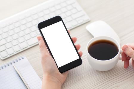 Mains femme tenant le téléphone avec écran isolé et tasse de café dans le bureau