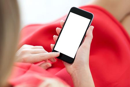 Frau im roten Kleid sitzt auf einem Sofa und hält ein Telefon mit isolierten Bildschirm Standard-Bild - 33668092