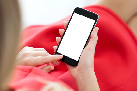 woman in red dress sitting on a sofa and holding a phone with isolated screen