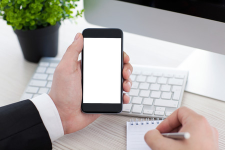 businessman sitting in the office holding phone with isolated screen and writing in a notebook
