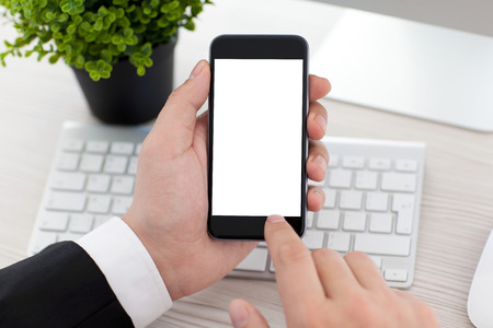 businessman sitting at the desk in office and holding phone with isolated screen Stock Photo