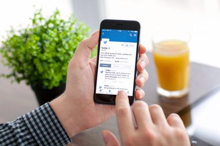 Alushta, Rusland - 21 november 2014: Man die een iPhone 6 Space Grijs met social networking dienst Twitter op het scherm. iPhone 6 werd gecreëerd en ontwikkeld door Apple inc. Redactioneel