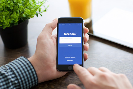 social networking service: Alushta, Rusia - 21 de noviembre 2014: Hombre que sostiene un espacio gris iPhone 6 con servicio de red social Facebook en la pantalla. iPhone 6 fue creado y desarrollado por Apple inc.