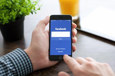 Alushta, Rusland - 21 november 2014: Man die een iPhone 6 Space Grijs met dienst voor sociale netwerken Facebook op het scherm. iPhone 6 werd gecreëerd en ontwikkeld door Apple inc.