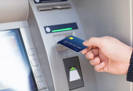 main de l'homme met carte de crédit dans l'ATM