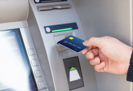 atm: man hand puts credit card into ATM Stock Photo