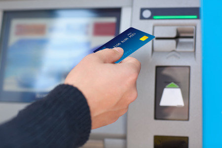 man hand puts credit card into ATM Stock Photo