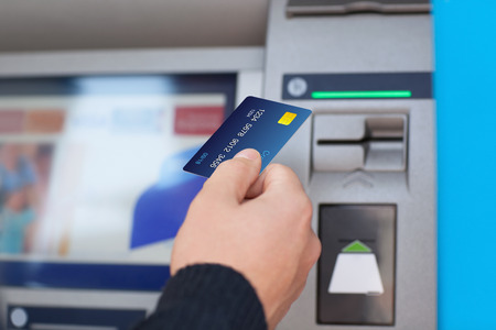 man hand zet creditcard in ATM