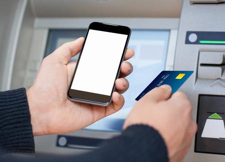 man die mobiele telefoon met geïsoleerde scherm en een creditcard bij een geldautomaat